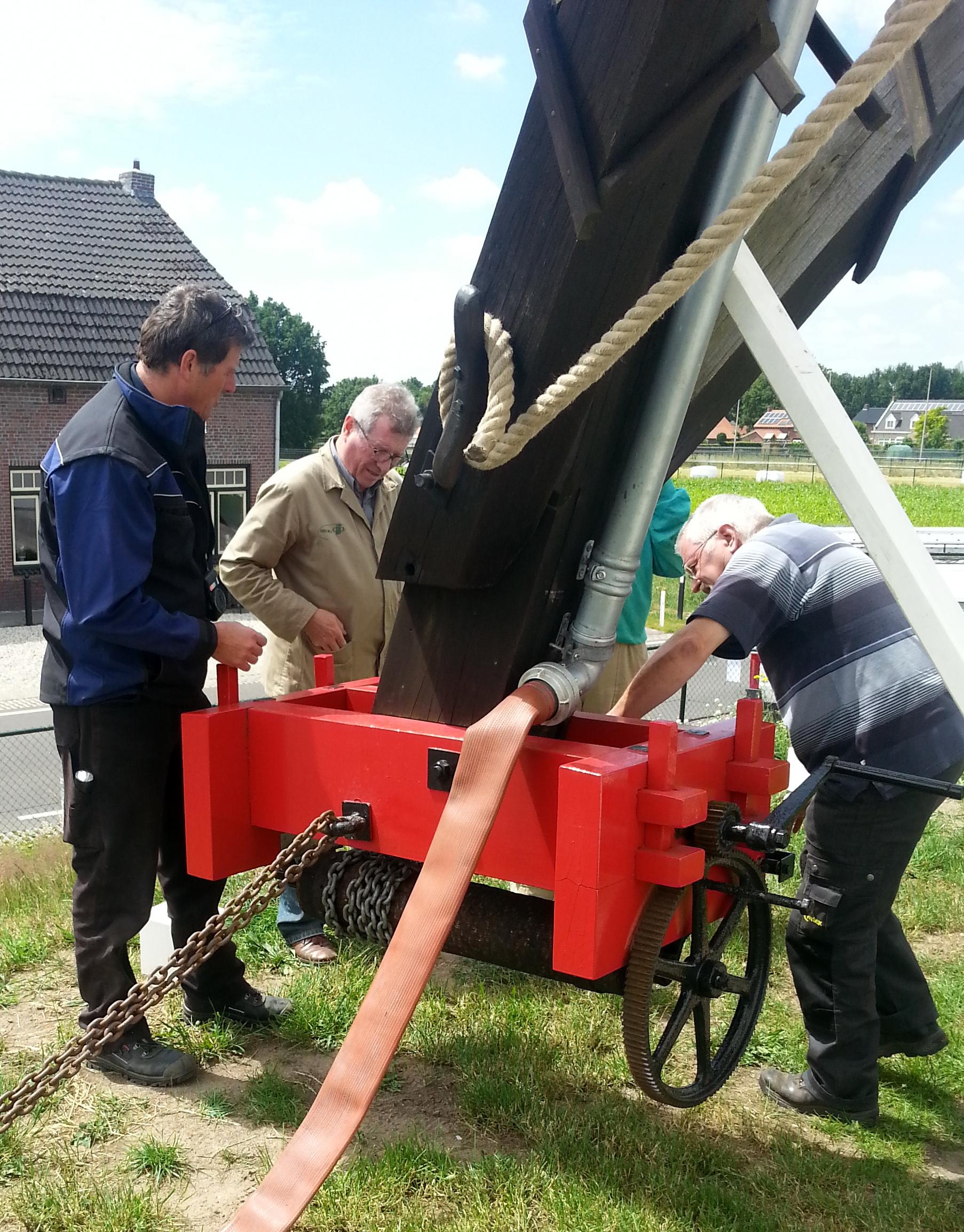 Inspecteur Beeren overlegt met de vrijwillige molenaars hoe een probleem dat tijdens het kruien van de molens soms optreedt, kan worden verholpen.